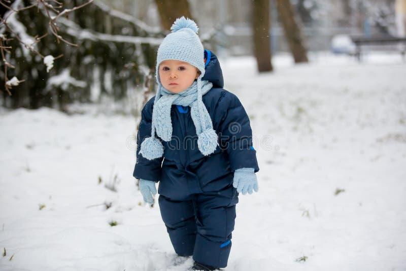 逗人喜爱的矮小的小孩男孩,使用户外与雪在一个冬日 库存照片