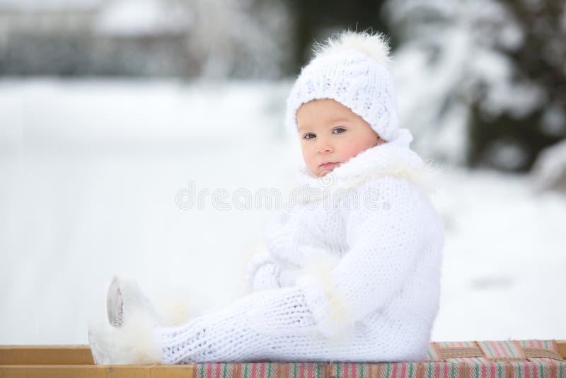 逗人喜爱的矮小的小孩男孩,使用户外与雪在一个冬日 免版税库存照片