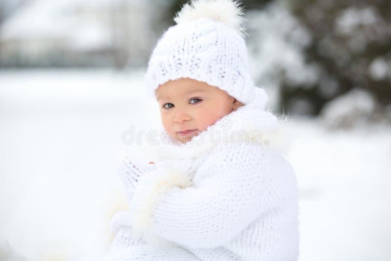 逗人喜爱的矮小的小孩男孩,使用户外与雪在一个冬日 库存图片