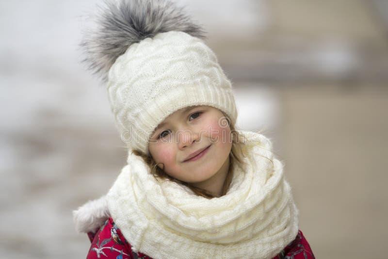 逗人喜爱的矮小的年轻滑稽的俏丽的微笑的白肤金发的儿童女孩画象有灰色眼睛的在白色明亮的bl的精密温暖的冬天衣物 库存照片