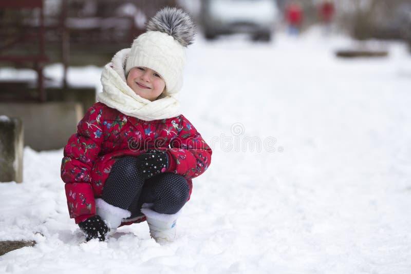 逗人喜爱的矮小的年轻滑稽的微笑的儿童女孩画象使用在雪的精密温暖的衣物的获得乐趣在丝毫的冬天冷的天 免版税图库摄影