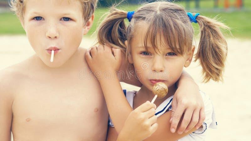 逗人喜爱的矮小的拉丁女孩和白种人男孩搂颈亲热与五颜六色的糖果在嘴在热带海滩假期 免版税库存图片