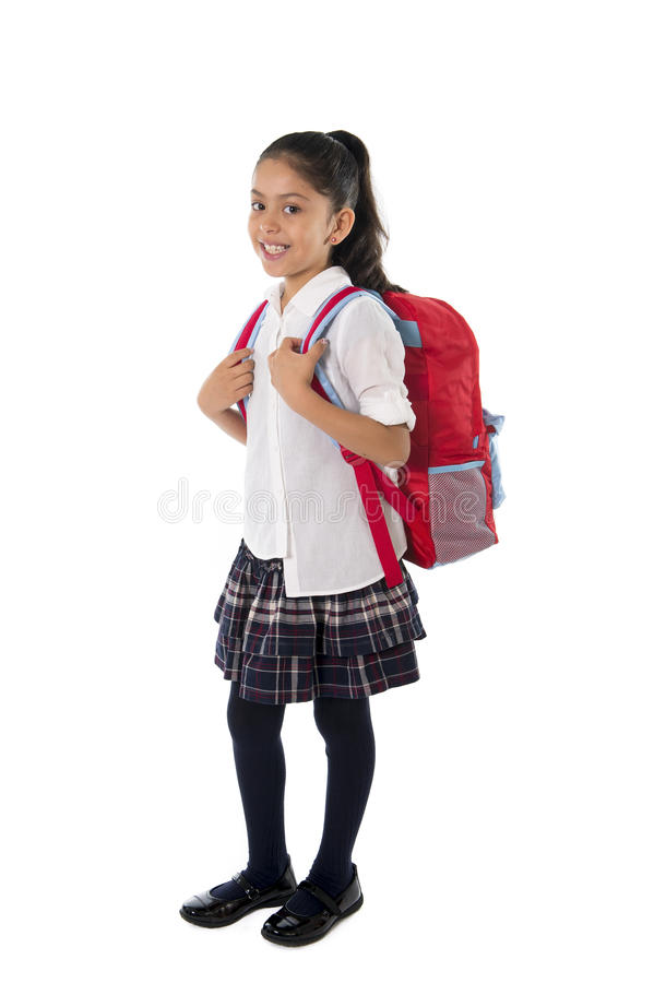 逗人喜爱的矮小的拉丁学校女孩运载的书包背包和书微笑 库存图片