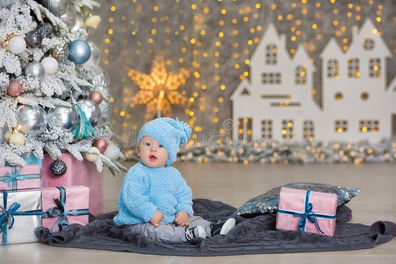 逗人喜爱的矮小的新出生的男婴圣诞节画象,穿戴在圣诞节衣裳和佩带的圣诞老人帽子,演播室射击,冬时 库存图片