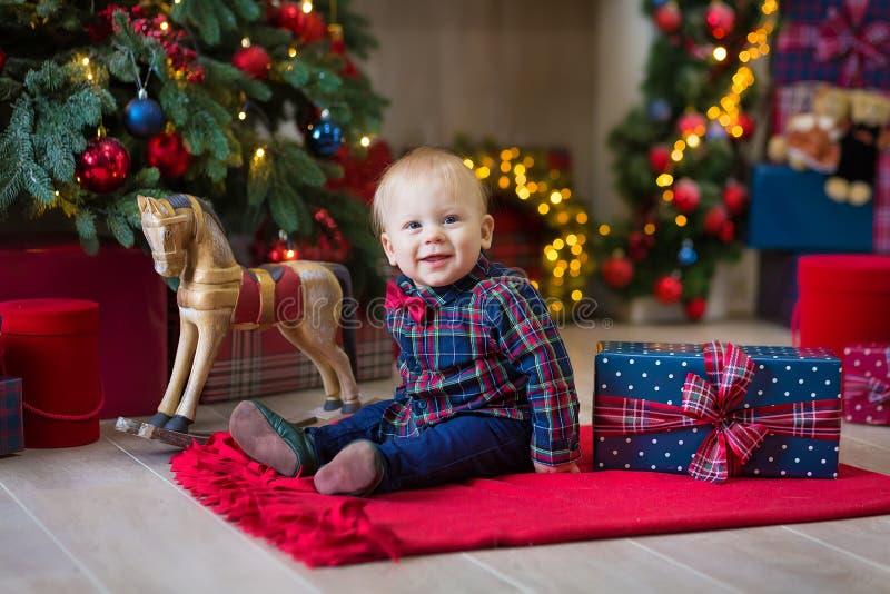 逗人喜爱的矮小的新出生的男婴圣诞节画象,穿戴在圣诞节衣裳和佩带的圣诞老人帽子,演播室射击,冬时 免版税库存照片