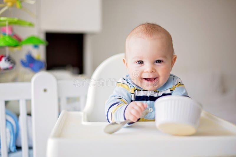逗人喜爱的矮小的男婴,吃午餐的被捣碎的菜,妈妈fe 库存图片