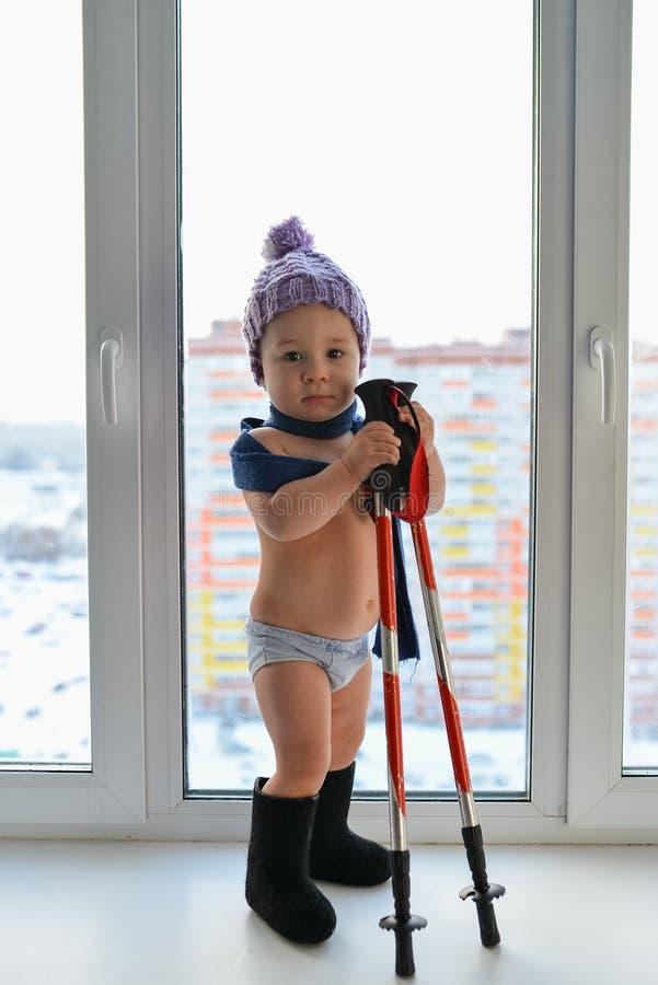 逗人喜爱的矮小的男婴在使用用迁徙的棍子站立在窗口附近,在backgr的高城市大厦的冬天衣裳weared 免版税库存照片