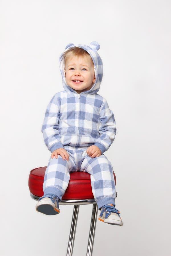 逗人喜爱的矮小的男婴坐红色椅子和微笑 库存照片