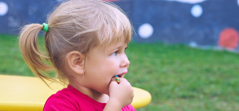逗人喜爱的矮小的白种人女孩在美好的夏日喜欢吃泡泡糖在幼儿园操场 库存图片