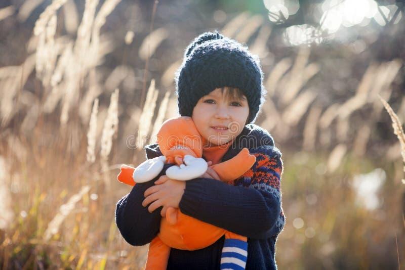 逗人喜爱的矮小的白种人孩子,男孩,拿着蓬松玩具,拥抱它 库存照片