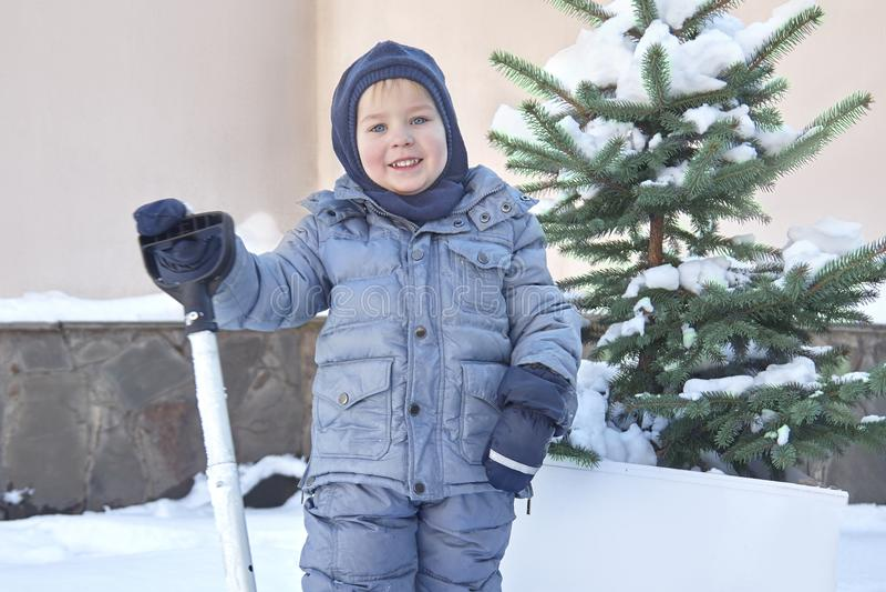 逗人喜爱的矮小的白种人男婴在有冷杉木的围场铲起雪在背景 冬天户外,微笑,桃红色面颊 Childr 免版税库存照片