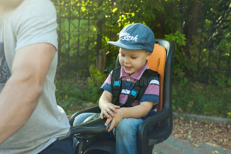 逗人喜爱的矮小的白种人画象3岁在位子自行车的小孩男婴儿童佩带的盖帽在父亲后,户外 图库摄影