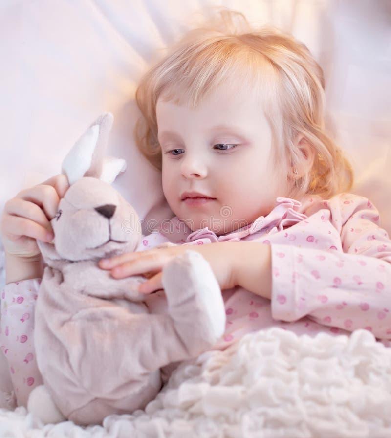 逗人喜爱的矮小的白肤金发的女孩作用用玩具兔子在河床上。 查找不适。 免版税库存照片