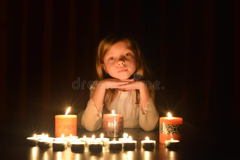 逗人喜爱的矮小的白肤金发的女孩保留她的手在下巴下 许多蜡烛是在她附近,在黑暗的背景 图库摄影