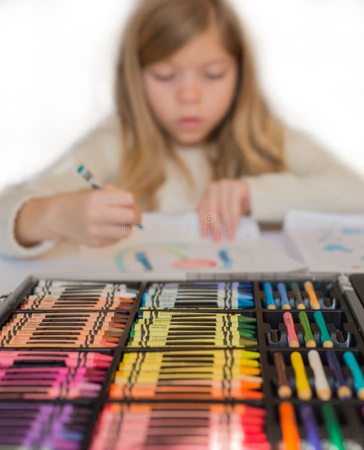 逗人喜爱的矮小的白肤金发的女孩由五颜六色的铅笔,箱在前景的铅笔画 库存照片