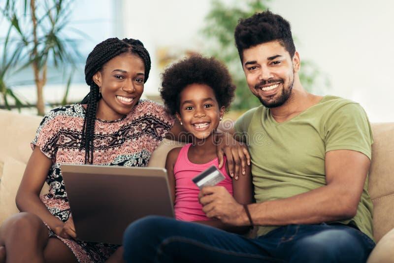 逗人喜爱的矮小的美国黑人的女孩和她使用膝上型计算机的美好的年轻父母 库存图片