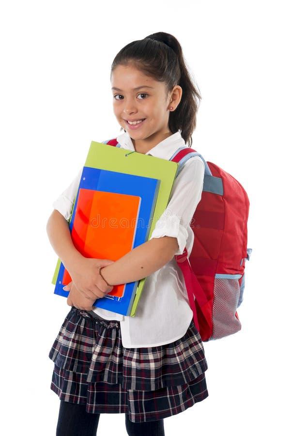 逗人喜爱的矮小的西班牙学校女孩运载的书包背包和书微笑 库存照片