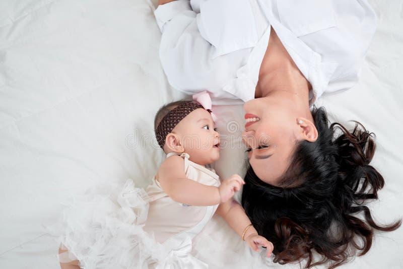 逗人喜爱的矮小的说谎在地板上的女婴和她的母亲 库存图片