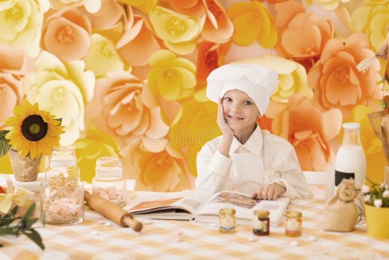逗人喜爱的矮小的婴孩在厨房里准备鲜美饭食 免版税图库摄影
