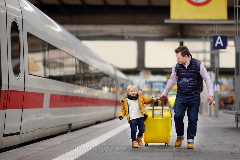 逗人喜爱的等待在火车站平台的小男孩和他的父亲快车 免版税库存照片