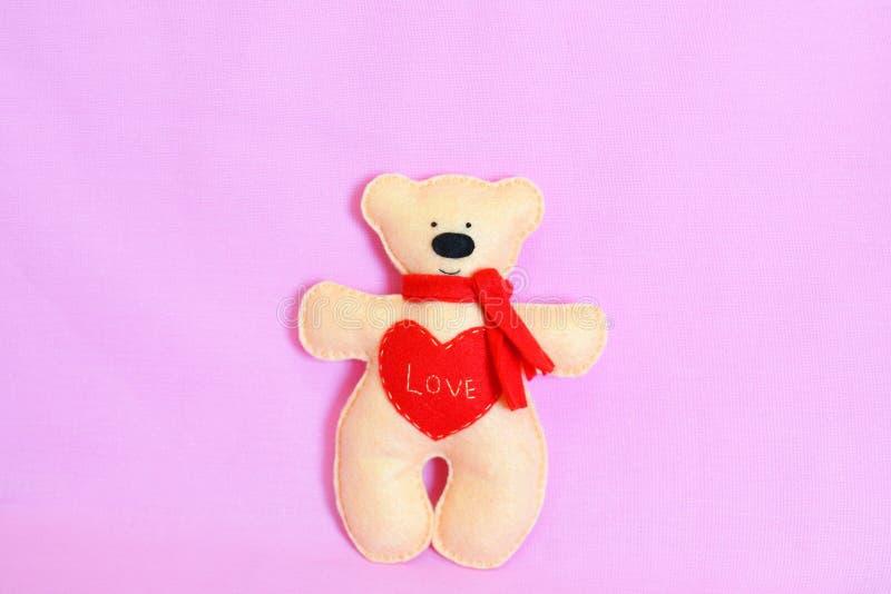 逗人喜爱的米黄女用连杉衬裤涉及桃红色背景 与一条红色围巾的感觉的米黄充满词爱的熊和心脏 Valentine& x27; s天工艺 库存照片