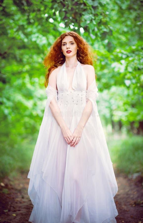 逗人喜爱的红发妇女佩带的白色礼服在庭院里 库存图片
