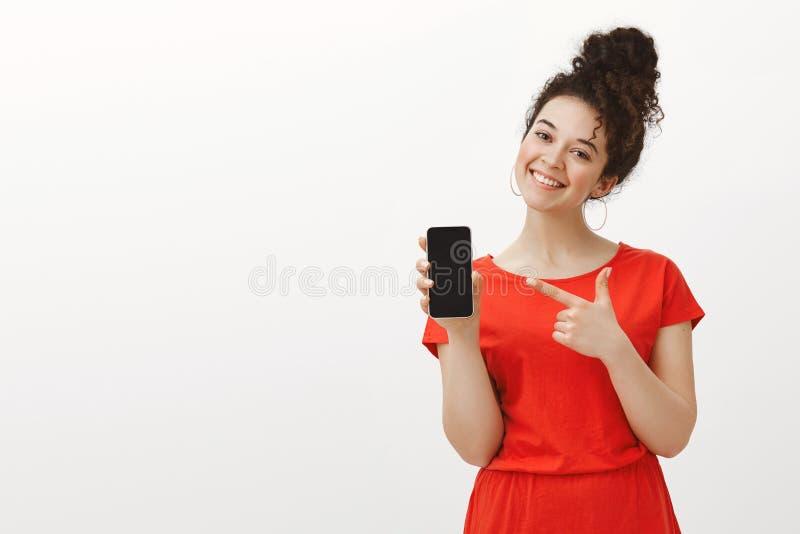 逗人喜爱的红色礼服的喜悦的无忧无虑的女朋友,显示智能手机和广泛地微笑与被掀动的头,当指向在时 库存照片