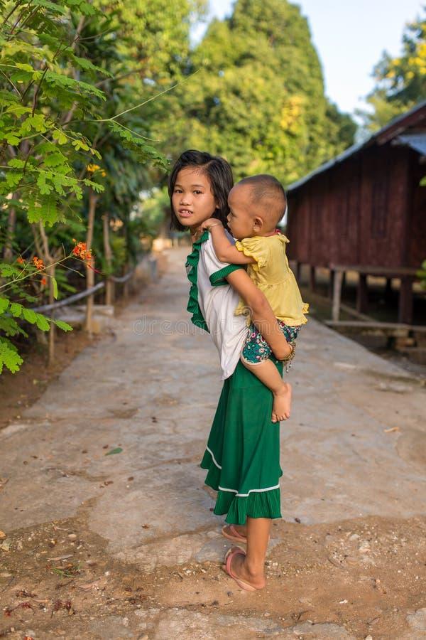 逗人喜爱的缅甸女孩在乡区的运载小男孩在缅甸 库存照片