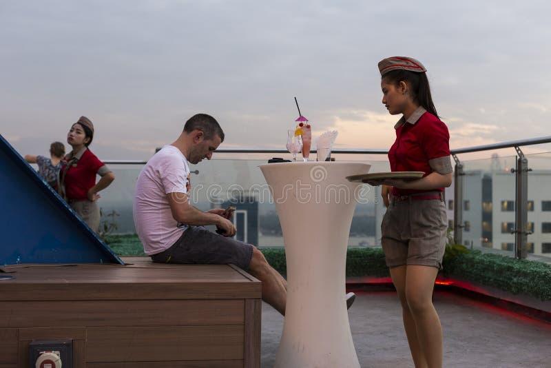 逗人喜爱的缅甸女服务员简而言之等待游人的支付他的在露天大阳台酒吧的饮料 图库摄影
