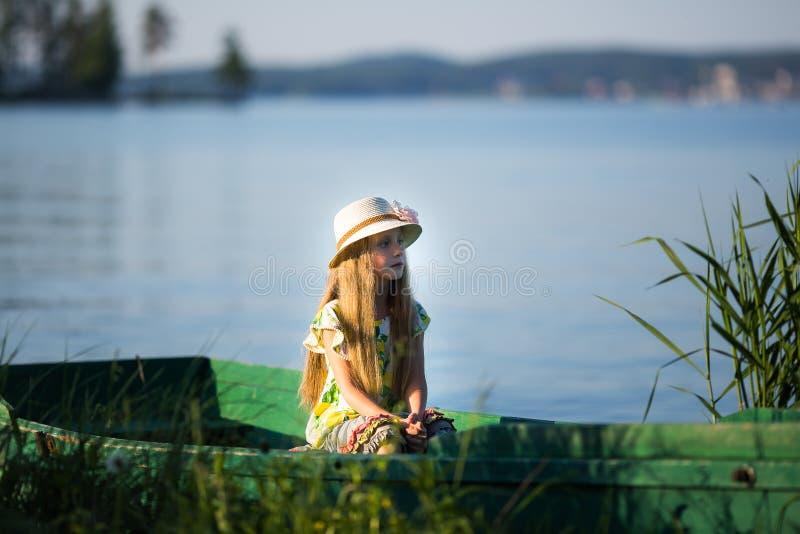 逗人喜爱的美丽的女孩在小船坐湖 库存照片