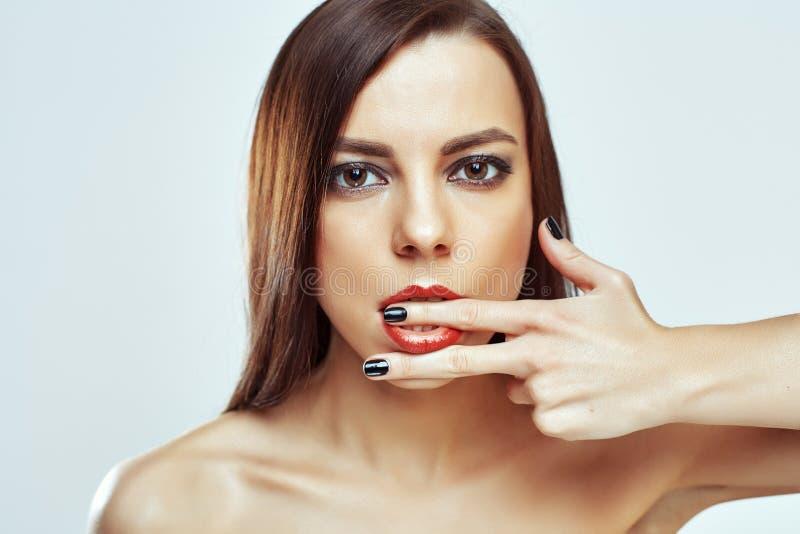 逗人喜爱的美丽的女孩画象有手指的在她的嘴 库存照片