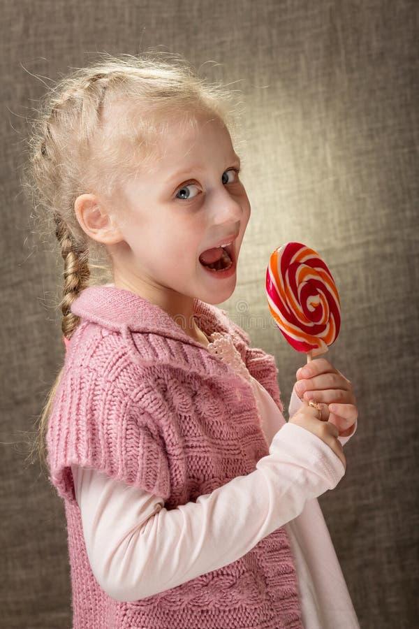逗人喜爱的美丽的白肤金发的女孩藏品棒棒糖 明亮的纵向 库存图片