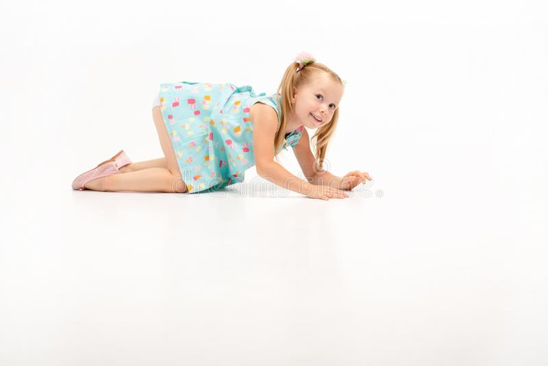 逗人喜爱的美丽的矮小的白肤金发的女孩在她的膝盖爬行,她休息与他们 免版税图库摄影