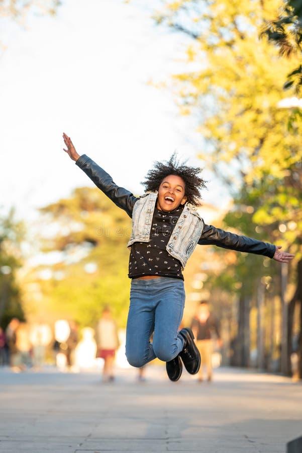 逗人喜爱的美国黑人的少年跳跃的户外 图库摄影