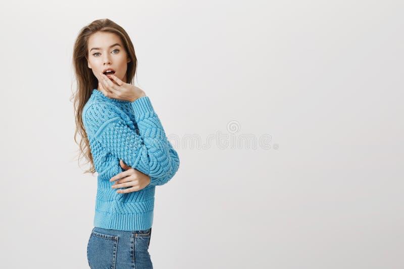 逗人喜爱的蓝色毛线衣身分的意想不到的欧洲妇女半转动了与惊奇的和嫩表示,藏品手 免版税库存图片