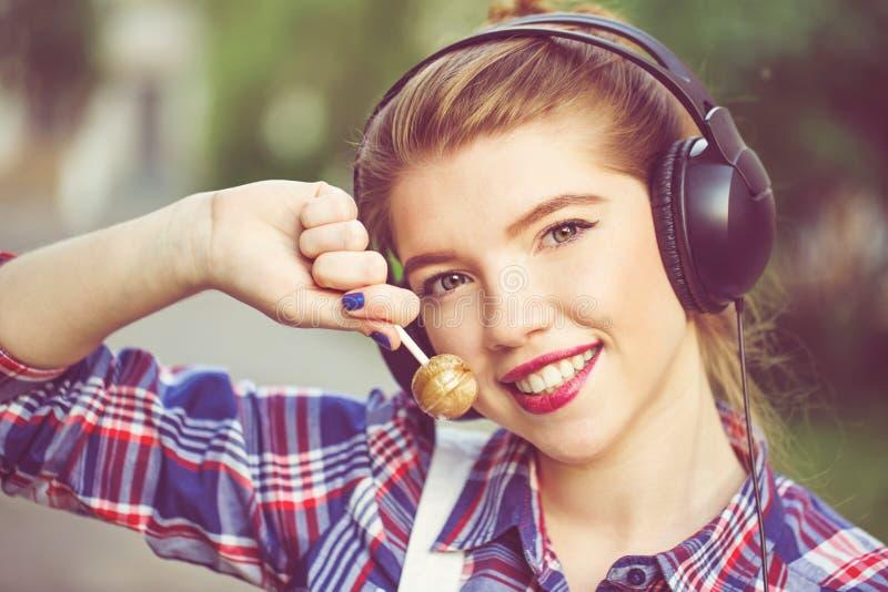 逗人喜爱的行家女孩画象有耳机和棒棒糖的 免版税库存图片
