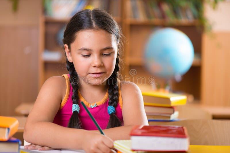 逗人喜爱的西班牙女孩在教室在学校 免版税库存图片