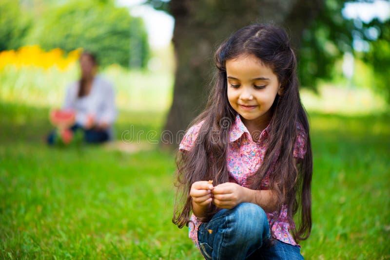 逗人喜爱的西班牙女孩在有母亲的公园背景的 免版税库存图片