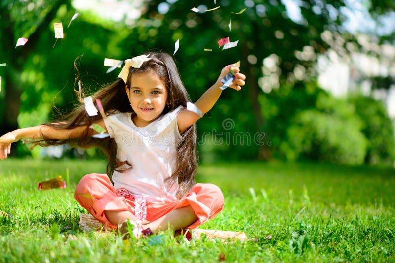 逗人喜爱的西班牙女孩投掷的五彩纸屑 免版税库存图片