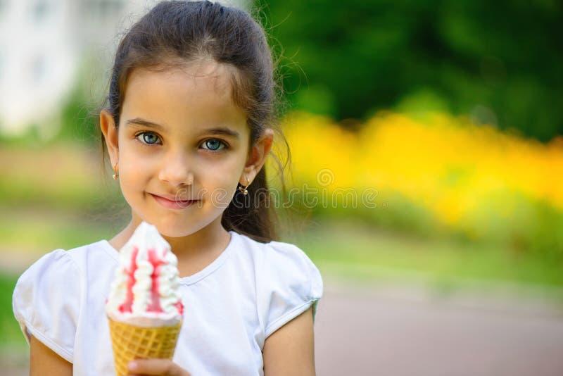 逗人喜爱的西班牙女孩用在公园的冰淇凌 库存图片