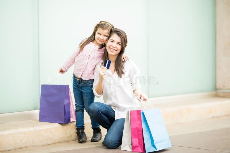 逗人喜爱的西班牙显示信用卡的母亲和女儿 免版税库存照片
