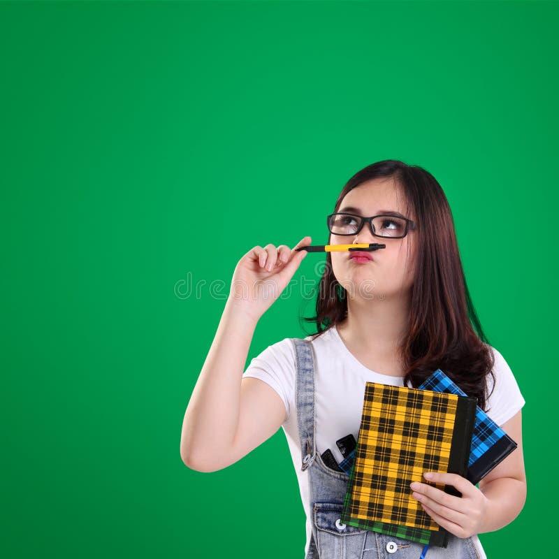 逗人喜爱的讨厌的女孩神色在绿色背景顶部 免版税图库摄影