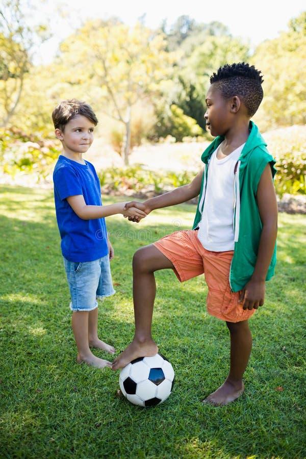 逗人喜爱的足球运动员握手画象  免版税库存图片