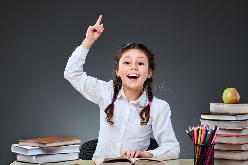 逗人喜爱的辛勤孩子坐在书桌户内 孩子在黑板背景的类学会  库存图片