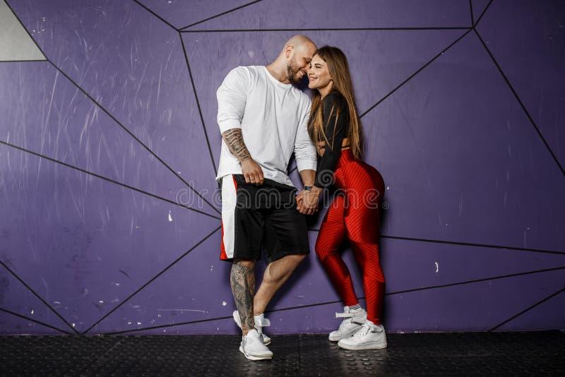 逗人喜爱的运动夫妇 苗条美女和坚强的运动人体育衣裳的在背景拥抱  免版税图库摄影