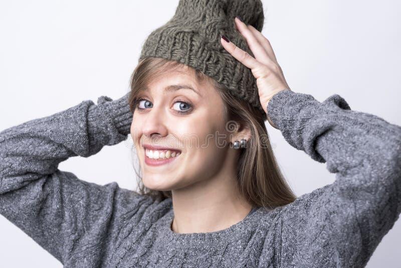 逗人喜爱的迷人的愉快的妇女投入了盖帽为寒冷冬天天气做准备 免版税库存照片