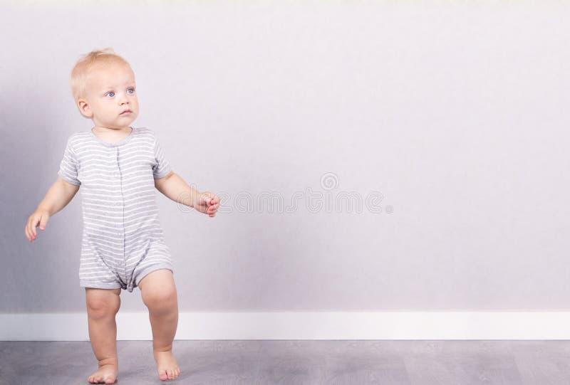逗人喜爱的金发碧眼的女人一个年孩子蹒跚反对灰色背景 复制空间 库存照片