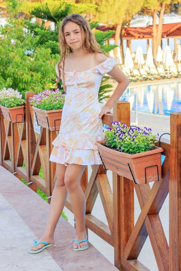 逗人喜爱的青少年的女孩一件浪漫礼服的和有长发的在桥梁站立在水池旁边 库存图片