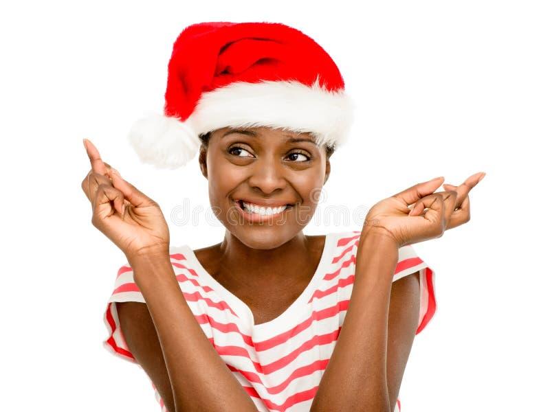 逗人喜爱的非裔美国人的女孩手指横渡了佩带的圣诞节帽子 免版税库存图片