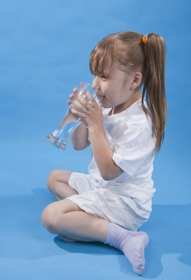 逗人喜爱的饮用的女孩小的水 免版税库存图片